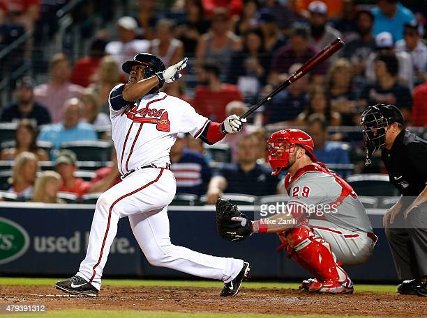Third baseman Juan Uribe of the Atlanta Braves hits a solo go ahead home run in the seventh inning as catcher Cameron Rupp of the Philadelphia...