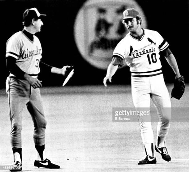 Third baseman Ken Oberkfell of the St Louis Cardinals hands part of a broken bat to third base coach Marry Warner of the Milwaukee Brewers during...