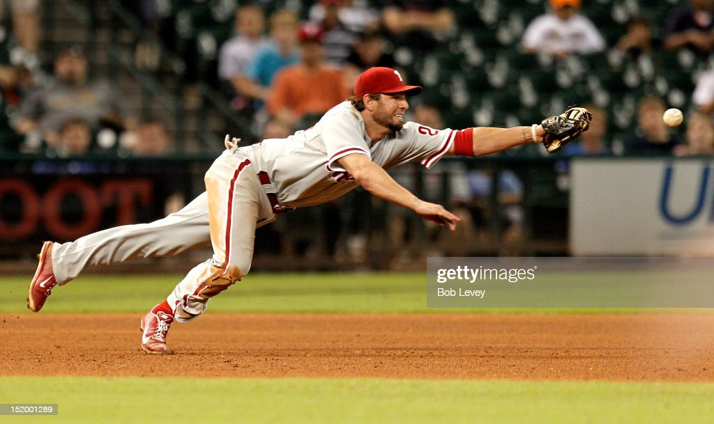 Third baseman <a gi-track='captionPersonalityLinkClicked' href=/galleries/search?phrase=Kevin+Frandsen&family=editorial&specificpeople=3982842 ng-click='$event.stopPropagation()'>Kevin Frandsen</a> #28 of the Philadelphia Phillies dives but can't make the stop on a ball hit by Jed Lowrie of the Houston Astros at Minute Maid Park on September 14, 2012 in Houston, Texas.