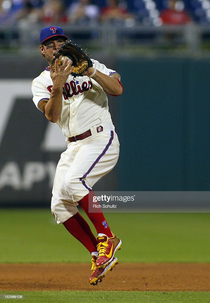 Third baseman <a gi-track='captionPersonalityLinkClicked' href=/galleries/search?phrase=Kevin+Frandsen&family=editorial&specificpeople=3982842 ng-click='$event.stopPropagation()'>Kevin Frandsen</a> #28 of the Philadelphia Phillies fields a ground ball and throws out Dan Uggla #26 the Atlanta Braves during the ninth inning of a MLB baseball game on September 22, 2012 at Citizens Bank Park in Philadelphia, Pennsylvania. The Braves defeated the Phillies 8-2.