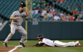 Third baseman Kevin Youkilis of the Boston Red Sox makes the catch as Brian Roberts of the Baltimore Orioles safely steals third base during the...
