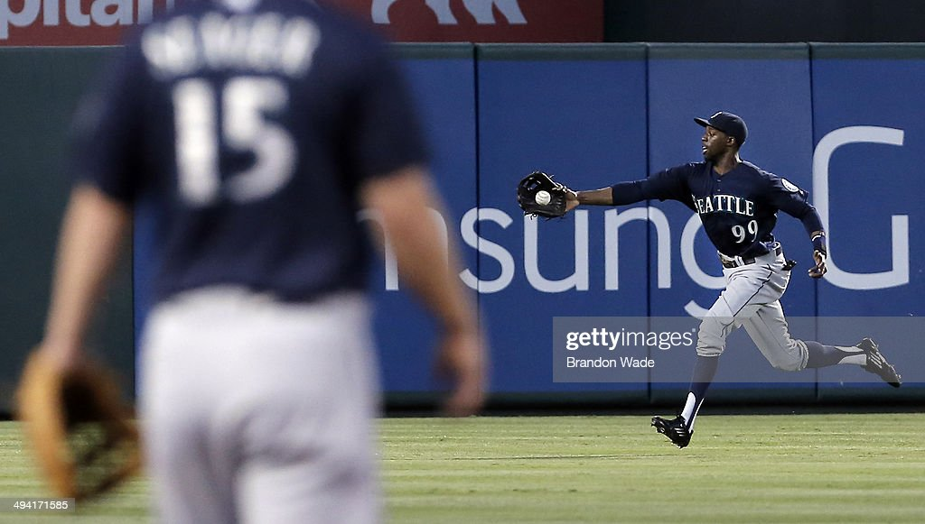 Third baseman Kyle Seager of the Seattle Mariners looks on as center fielder James Jones reaches for the ball on a RBI single hit by Alex Rios of the...