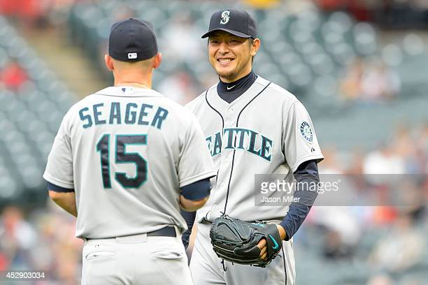 Third baseman Kyle Seager talks with starting pitcher Hisashi Iwakuma of the Seattle Mariners after Iwakuma fielded an infield pop fly hit by David...