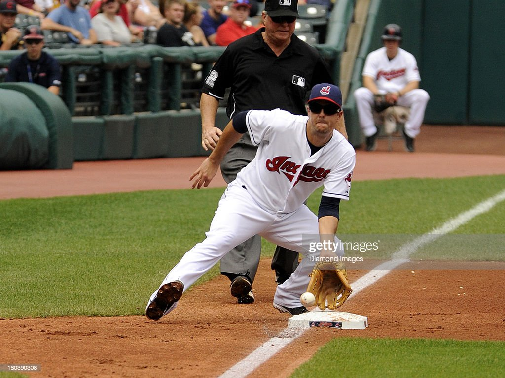 Third baseman Lonnie Chisenhall #8 of the Cleveland Indians reaches for a throw from catcher Yan Gomes #10 in attempt to stop a stolen base attempt during a game against the Kansas City Royals on September 11, 2013 at Progressive Field in Cleveland, Ohio. Kansas City won 6-2.