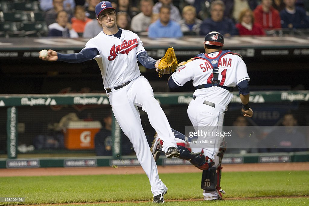 Third baseman <a gi-track='captionPersonalityLinkClicked' href=/galleries/search?phrase=Lonnie+Chisenhall&family=editorial&specificpeople=6796448 ng-click='$event.stopPropagation()'>Lonnie Chisenhall</a> #8 throws to first with back up from catcher Carlos Santana #41 of the Cleveland Indians during the sixth inning against the Chicago White Sox at Progressive Field on October 1, 2012 in Cleveland, Ohio.