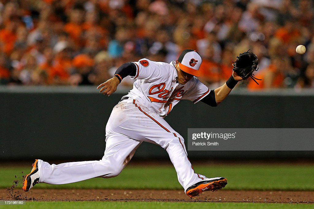 Third baseman <a gi-track='captionPersonalityLinkClicked' href=/galleries/search?phrase=Manny+Machado&family=editorial&specificpeople=5591039 ng-click='$event.stopPropagation()'>Manny Machado</a> #13 of the Baltimore Orioles cannot handle a hit by Elvis Andrus #1 of the Texas Rangers (not pictured) in the sixth inning at Oriole Park at Camden Yards on July 9, 2013 in Baltimore, Maryland. The Texas Rangers won, 8-4.