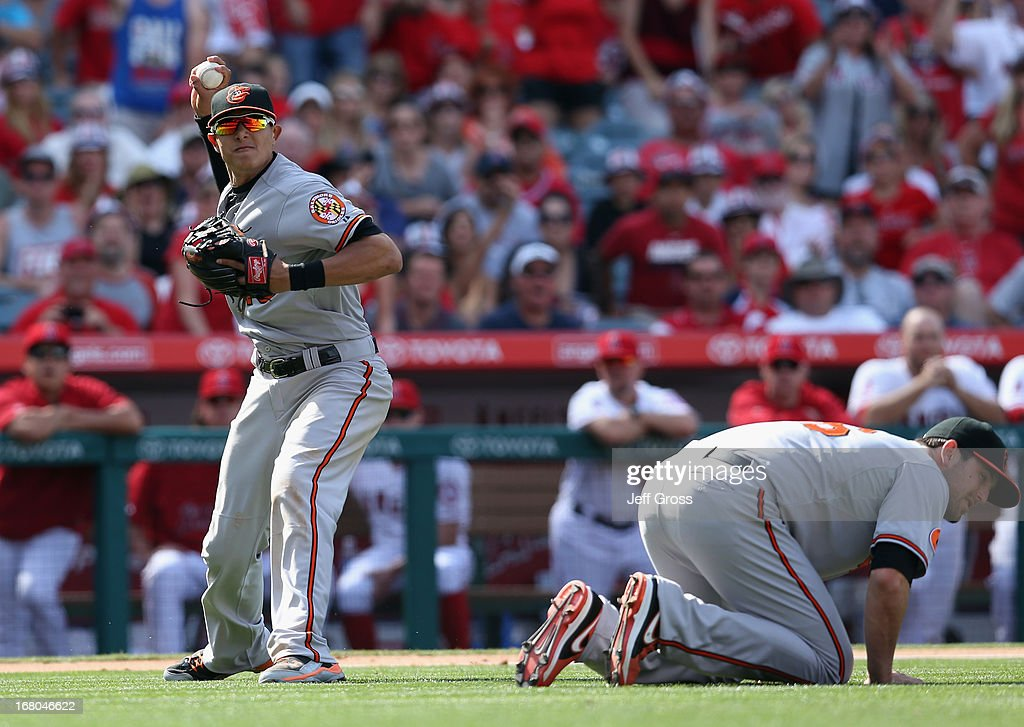 Third baseman <a gi-track='captionPersonalityLinkClicked' href=/galleries/search?phrase=Manny+Machado&family=editorial&specificpeople=5591039 ng-click='$event.stopPropagation()'>Manny Machado</a> #13 of the Baltimore Orioles throws to first base over pitcher <a gi-track='captionPersonalityLinkClicked' href=/galleries/search?phrase=Darren+O%27Day&family=editorial&specificpeople=4921679 ng-click='$event.stopPropagation()'>Darren O'Day</a> #56 in the eighth inning at Angel Stadium of Anaheim on May 4, 2013 in Anaheim, California. The Orioles defeated the Angels 5-4 in ten innings.