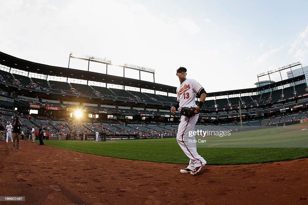 Third baseman Manny Machado #13 of the Baltimore Orioles walks to the dugout before the start of the Orioles game against the Tampa Bay Rays at Oriole Park at Camden Yards on April 18, 2013 in Baltimore, Maryland.