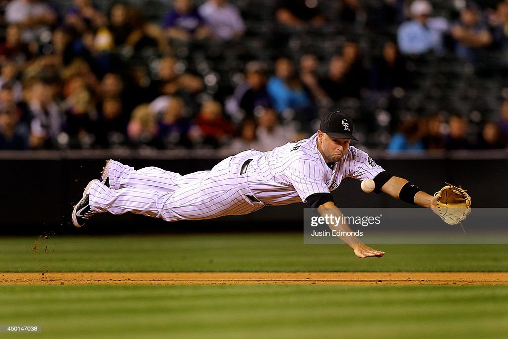 Third baseman <a gi-track='captionPersonalityLinkClicked' href=/galleries/search?phrase=Michael+Cuddyer&family=editorial&specificpeople=208127 ng-click='$event.stopPropagation()'>Michael Cuddyer</a> #3 of the Colorado Rockies dives but comes up short on a base hit by Miguel Montero (not pictured) of the Arizona Diamondbacks during the ninth inning at Coors Field on June 5, 2014 in Denver, Colorado.