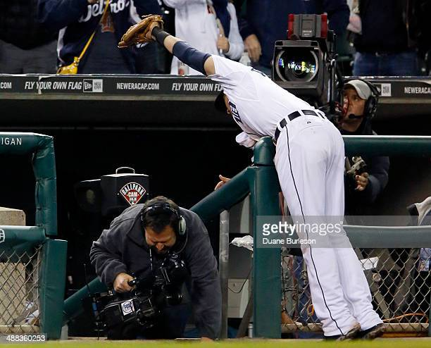 Third baseman Nick Castellanos of the Detroit Tigers reaches over the dugout to make the catch on a foul ball hit by Chris Carter of the Houston...