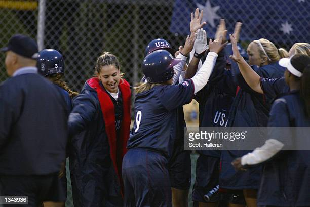 Third baseman Nina Lindenberg of the USA Softball team is greeted by teammates at home plate after hitting a tworun homerun in the second inning...