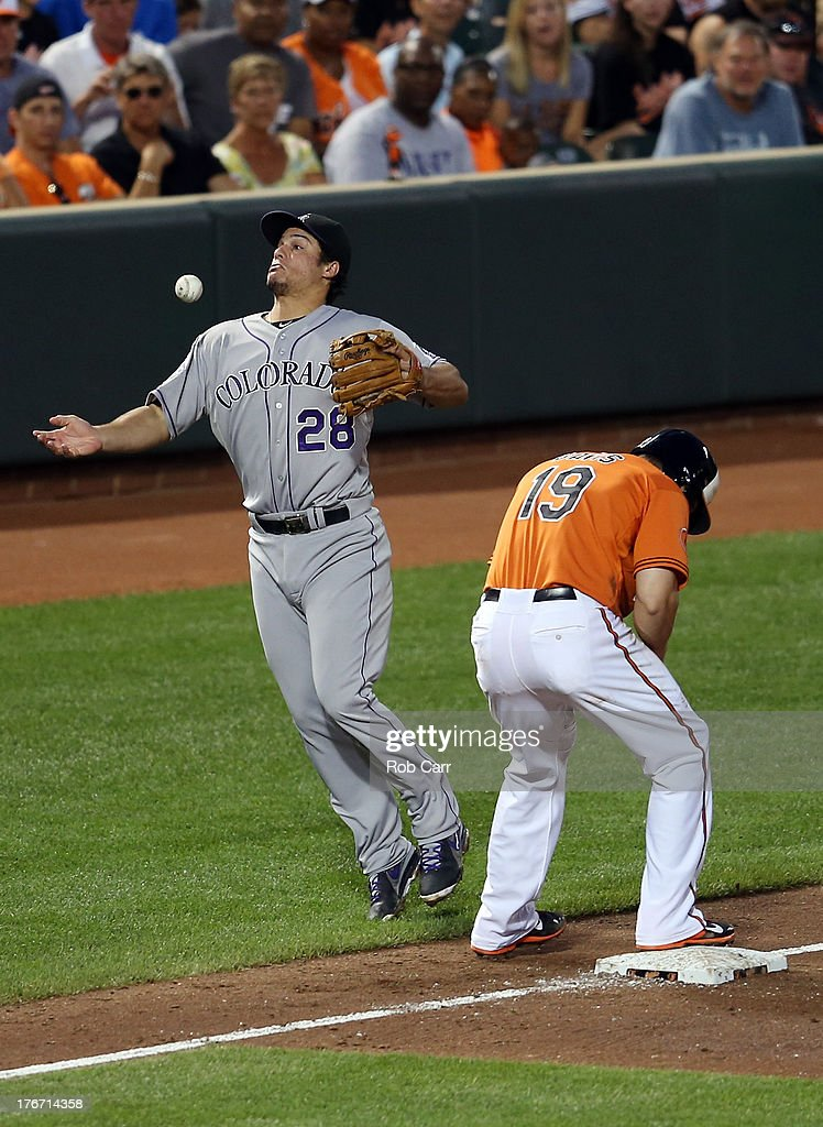 Third baseman Nolan Arenado #28 of the Colorado Rockies bobbles a ball hit for an infield single by Adam Jones #10 of the Baltimore Orioles Adam Jones (10) of the Baltimore Orioles (not pictured) in front of Chris Davis #19 during the third inning at Oriole Park at Camden Yards on August 17, 2013 in Baltimore, Maryland.