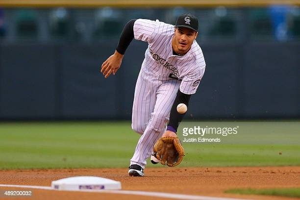 Third baseman Nolan Arenado of the Colorado Rockies fields a ground ball on his way to recording the second out of the first inning against the San...