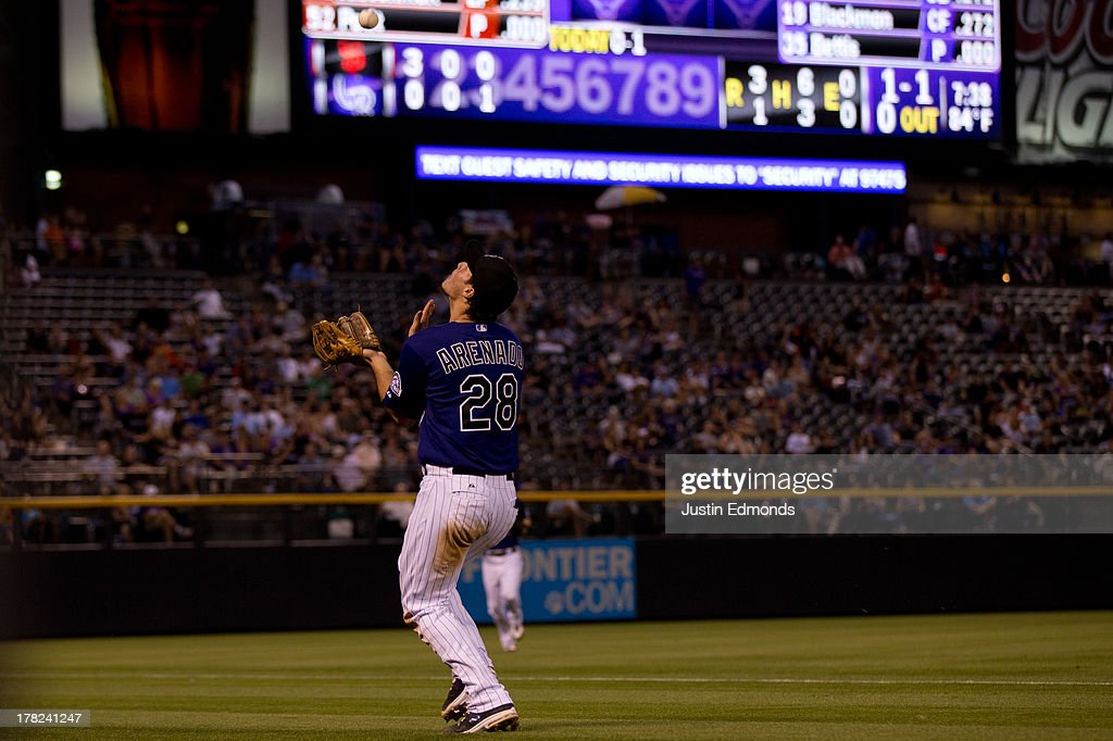 Third baseman Nolan Arenado #28 of the Colorado Rockies makes a catch on the run over his shoulder for the first out of the fourth inning against the San Francisco Giants at Coors Field on August 27, 2013 in Denver, Colorado. The Giants defeated the Rockies 5-3.