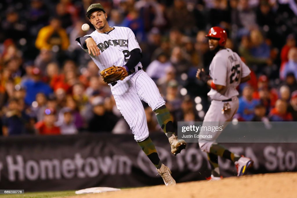 Third baseman Nolan Arenado #28 of the Colorado Rockies makes a throw on the run to first base for the third out of the ninth inning as Dexter Fowler #25 of the St Louis Cardinals looks on at Coors Field on May 27, 2017 in Denver, Colorado. The Cardinals defeated the Rockies 3-0.