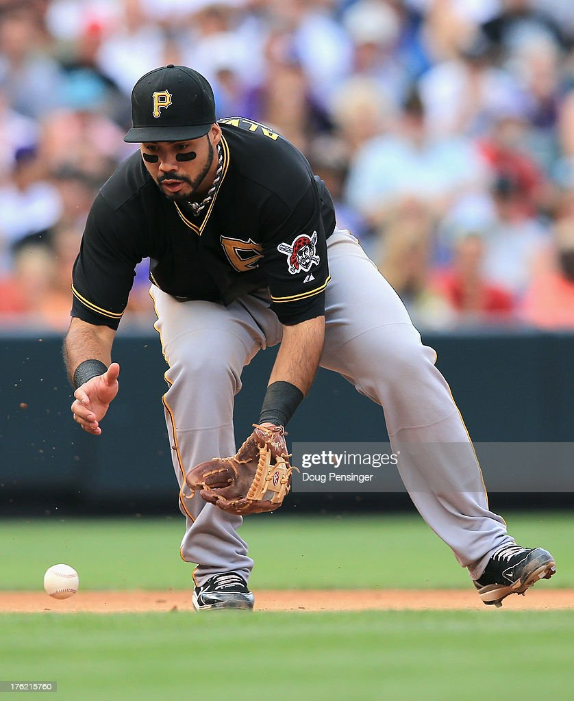 Third baseman Pedro Alvarez #24 of the Pittsburgh Pirates makes a throwing error on a ground ball by Corey Dickerson #6 of the Colorado Rockies that allowed Yorvit Torrealba #8 of the Colorado Rockies to score and even the game at 2-2 in the sixth inning at Coors Field on August 11, 2013 in Denver, Colorado. The Rockies defeated the Pirates 3-2.
