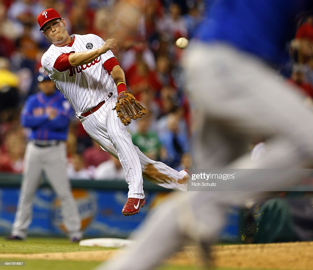 Third baseman <a gi-track='captionPersonalityLinkClicked' href=/galleries/search?phrase=Reid+Brignac&family=editorial&specificpeople=4175431 ng-click='$event.stopPropagation()'>Reid Brignac</a> #17 of the Philadelphia Phillies throws to first base but <a gi-track='captionPersonalityLinkClicked' href=/galleries/search?phrase=Juan+Lagares&family=editorial&specificpeople=8960493 ng-click='$event.stopPropagation()'>Juan Lagares</a> #12 of the New York Mets beats the throw for a single during the fifth inning in a game at Citizens Bank Park on May 30, 2014 in Philadelphia, Pennsylvania. The Phillies defeated the Mets 6-5 in fourteen innings.