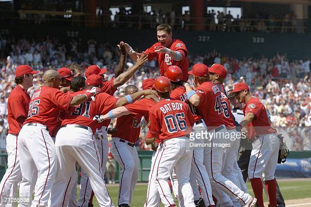 Third baseman Ryan Zimmerman of the Washington Nationals leaps into his teammates arms as he touches home plate after hitting a walkoff home run...