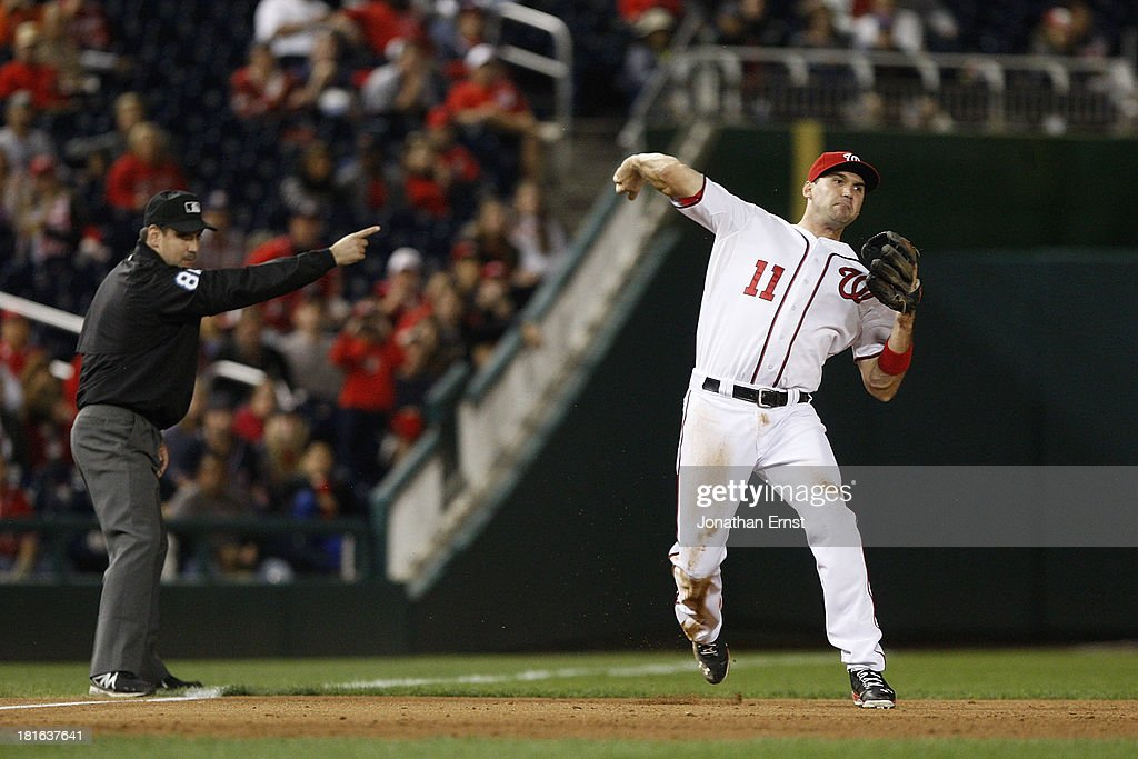Third baseman <a gi-track='captionPersonalityLinkClicked' href=/galleries/search?phrase=Ryan+Zimmerman+-+Baseball+Player&family=editorial&specificpeople=534809 ng-click='$event.stopPropagation()'>Ryan Zimmerman</a> #11 of the Washington Nationals throws out Giancarlo Stanton (not pictured) #27 of the Miami Marlins on a ground ball during the sixth inning of game 2 of their day-night doubleheader at Nationals Park on September 22, 2013 in Washington, DC. Also pictured is third base umpire David Rackley (L), signaling for a fair ball.