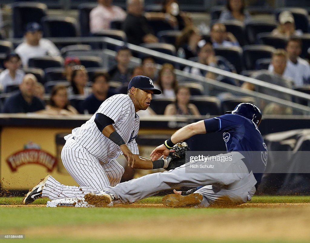 Third baseman <a gi-track='captionPersonalityLinkClicked' href=/galleries/search?phrase=Yangervis+Solarte&family=editorial&specificpeople=9013250 ng-click='$event.stopPropagation()'>Yangervis Solarte</a> #26 of the New York Yankees is late in applying the tag as <a gi-track='captionPersonalityLinkClicked' href=/galleries/search?phrase=Evan+Longoria&family=editorial&specificpeople=2349329 ng-click='$event.stopPropagation()'>Evan Longoria</a> #3 of the Tampa Bay Rays slides into third on a single by James Loney (not pictured) in the eighth inning of a MLB baseball game at Yankee Stadium on July 1, 2014 in the Bronx borough of New York City. The Rays defeated the Yankees 2-1.