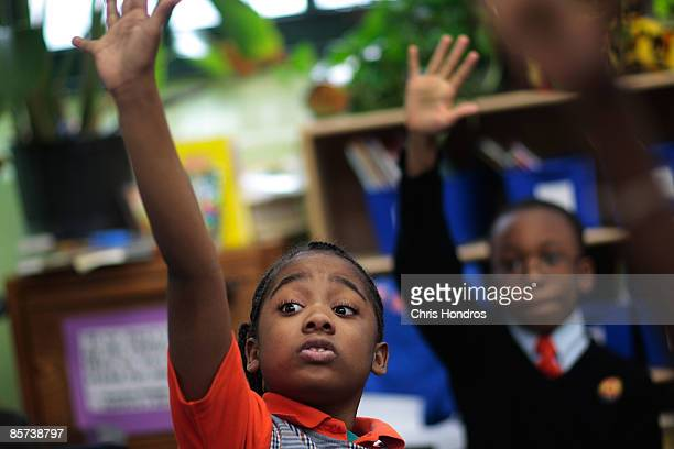 Third grade students Tyler Smalls and Sekou Cisse raise their hands in reading comprehension class at Harlem Success Academy a free public elementary...