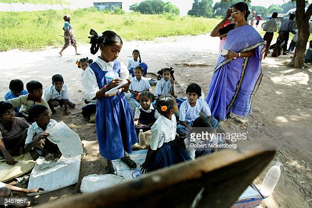 Third grade students watch as their teacher corrects a text book exercise in a rural school's science class under a Tamarind tree November 11 2003 in...