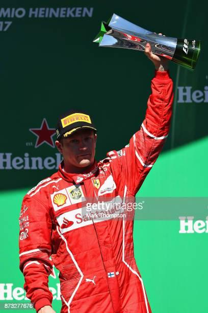 Third place finisher Kimi Raikkonen of Finland and Ferrari celebrates on the podium during the Formula One Grand Prix of Brazil at Autodromo Jose...