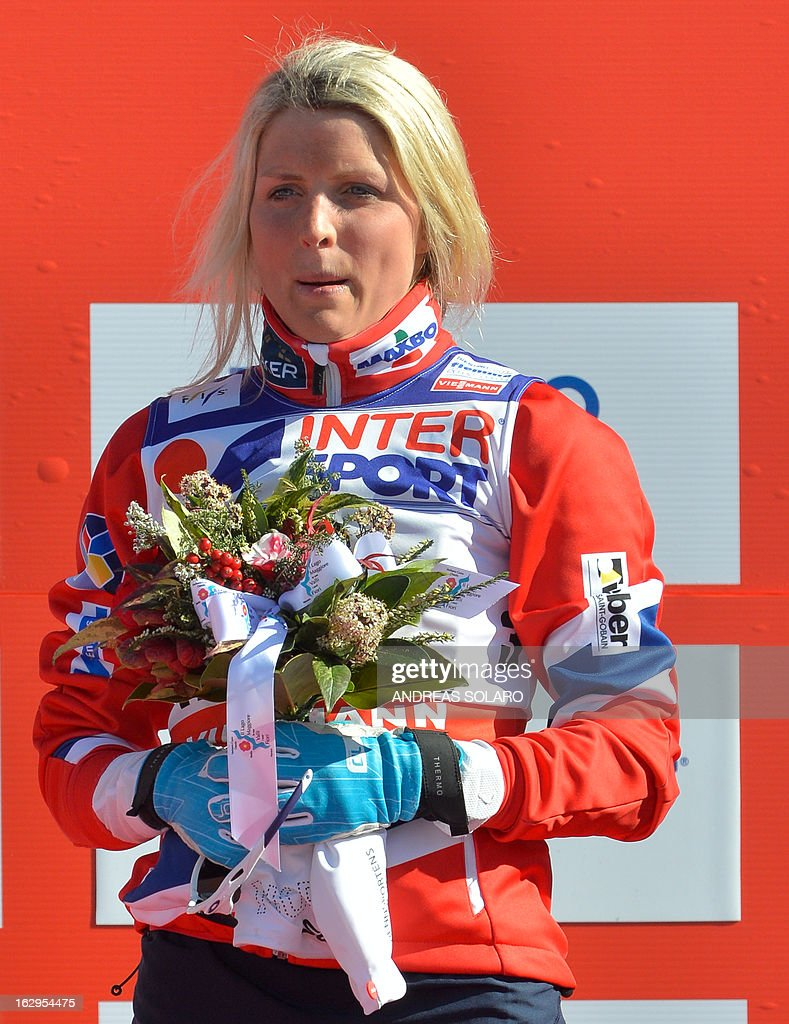 Third place Norway's Therese Johaug celebrates, on March 2, 2013, on the podium of the Women's Cross Country 30 km Classic race of the FIS Nordic World Ski Championships at Val Di Fiemme Cross Country stadium in Cavalese, northern Italy.