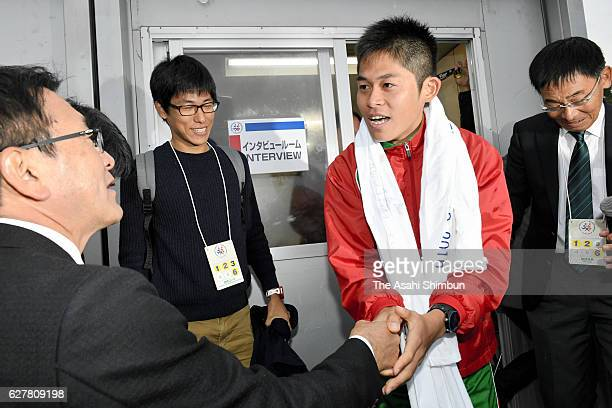 Third place Yuki Kawauchi of Japan shakes hands with former runner Toshihiko Seko after competing in the Fukuoka International Marathon at Heiwadai...