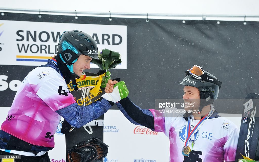 Third placed Austria's Markus Schairer (R) and his teammate Alessandro Haemmerle (first place) celebrate on the podium after the Snowboard Cross World Cup Men's Test Event at the Snowboard and Freestyle Center in Rosa Khutor near the Black Sea resort of Sochi, on February 17, 2013.