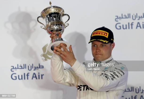 Third placed driver Valtteri Bottas of Finland and Mercedes GP celebrates with his trophy on the podium during the Bahrain Formula One Grand Prix at...