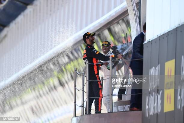 Third placed finisher Daniel Ricciardo of Australia and Red Bull Racing and race winner Lewis Hamilton of Great Britain and Mercedes GP celebrate on...