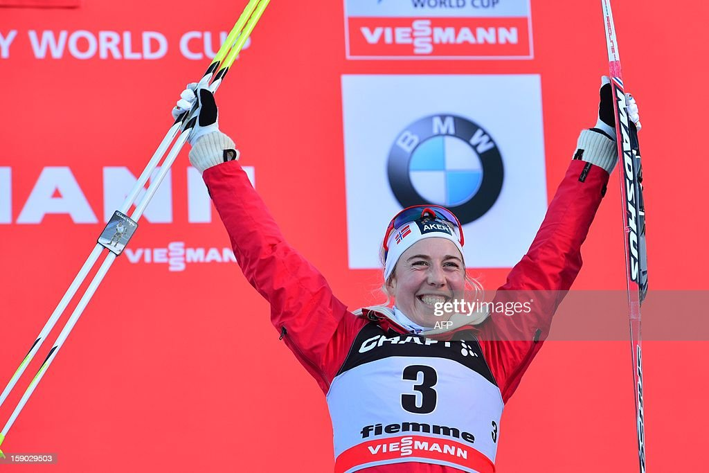 Third placed Kristin Stoermer Steira of Norway celebrates on the podium of the women's 9km free final climb pursuit of the Tour de Ski in Val di Fiemme on January 6, 2013. Justyna Kowalczyk of Poland won the race ahead Therese Johaug of Norway and Kristin Stoermer Steira of Norway.