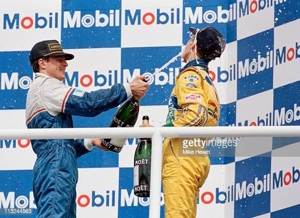 Third placed Mark Blundell driver of the Ligier Gitanes Blondes Ligier JS39 Renault 35 V10 sprays champagne over race winner Michael Schumacher...