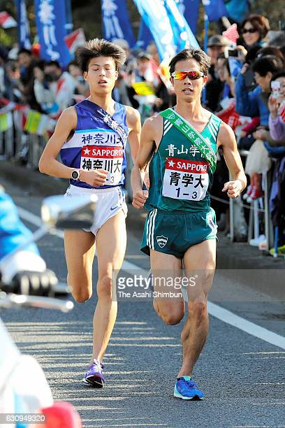 Third runner Yuhi Akiyama of Aoyama Gakuin University takes lead to Kenta Koshikawa of Kanagawa University during day one of the 93rd Hakone Ekiden...