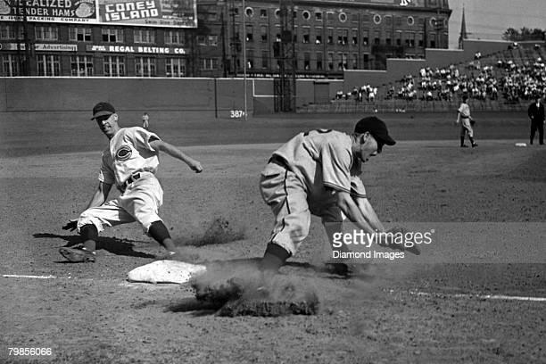 Thirdbaseman Bill Werber of the Cincinnati Reds steals thirdbase as thirdbaseman Frank Gustine of the Pittsburgh Pirates takes the late throw from...