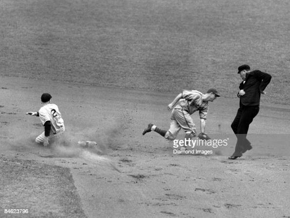Thirdbaseman Red Rolfe of the New York Yankees steals secondbase as shortstop Billy Jurges of the Chicago Cubs retrieves the errant throw from...