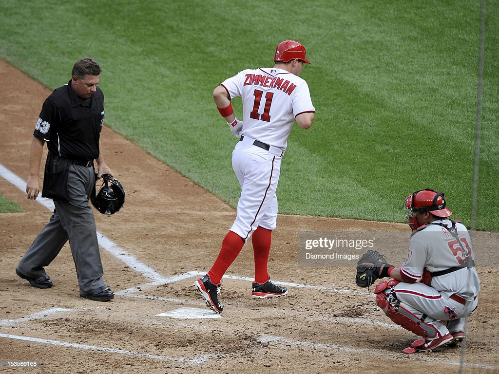 Thirdbaseman Ryan Zimmerman #11 (center) of the Washington Nationals touches homeplate after hitting a solo homerun off pitcher Cliff Lee of the Philadelphia Phillies leading off the bottom of the fourth inning of a game on October 3, 2012 at Nationals Park in Washington, DC. The homeplate umpire is Greg Gibson #53 (left) and the Phillies' catcher is Carlos Ruiz #51 (right). The Nationals beat the Phillies, 5-1 and clinched home field advantage throughout the post season.