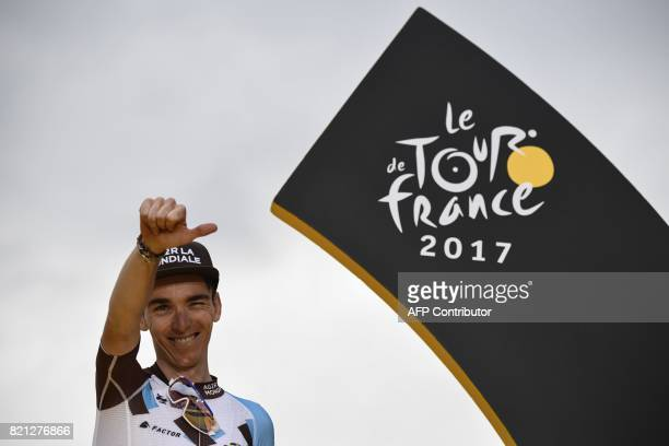 TOPSHOT Thirdplaced France's Romain Bardet celebrates on the podium on the ChampsElysees avenue in Paris at the end of the 103 km twentyfirst and...