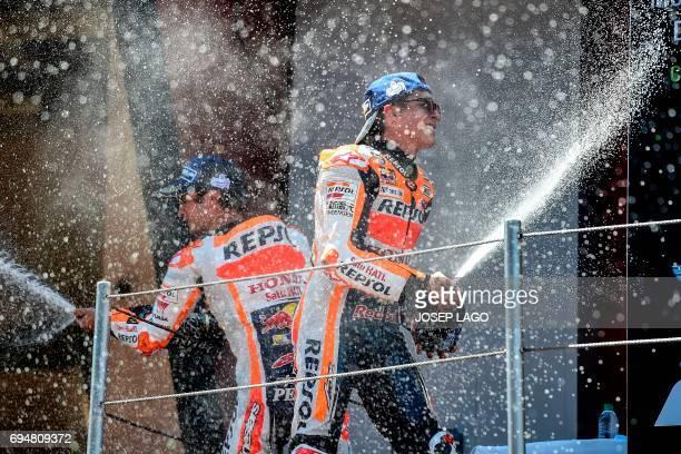 TOPSHOT Thirdplaced Repsol Honda Team's Spanish rider Dani Pedrosa and secondplaced Repsol Honda Team's Spanish rider Marc Marquez spary cava on the...