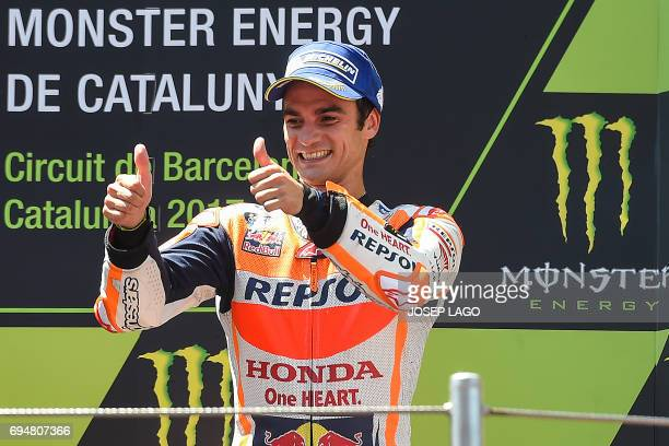 Thirdplaced Repsol Honda Team's Spanish rider Dani Pedrosa gives the thumbsup on the podium with the trophy after the Moto GP race of the Catalunya...
