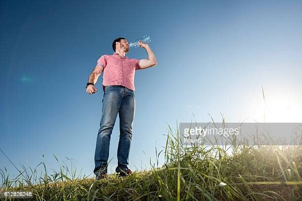 Thirsty man drinking water against the clear sky.