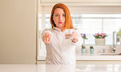 Thirsty redhead woman and glass of water pointing with finger to the camera and to you, hand sign, positive and confident gesture from the front