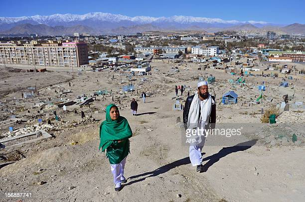 Thirteen year old Afghan girl Tarana Akbari walks with her father Ahmad Shah as they prepare to pray for Tarana's brother in their graveyard in the...