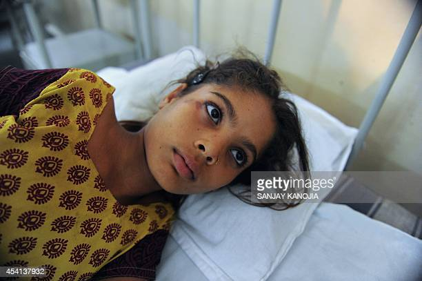 Thirteen yearold Indian girl Preeti lies on a bed in the Janki Kund Hospital following a stampede at the Kamta Nath Temple in Chitrakoot district of...