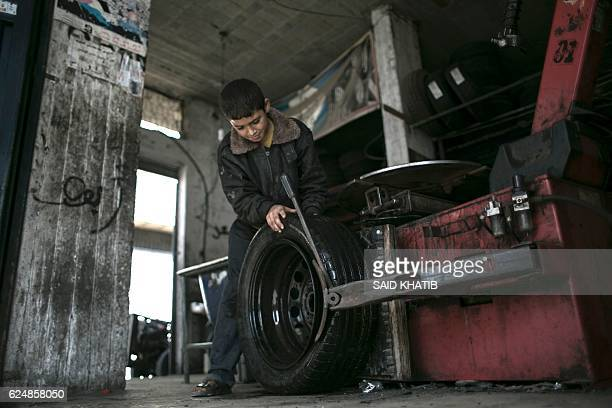Thirteenyearold Palestinian Odai Abu Matrouq works at a tyres workshop in Rafah in the southern Gaza strip on November 21 2016 The numbers of child...