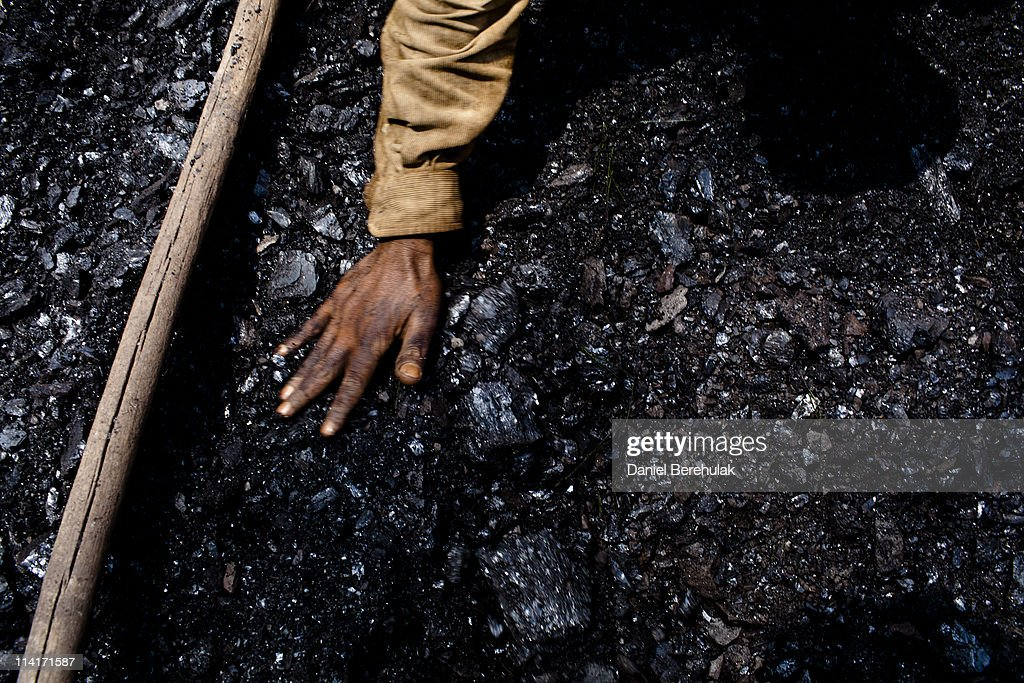 Thirty eight-year-old Prabhat Sinha, from Assam, levels out the coal in a crate on April 16, 2011 near the village of Khliehriat, in the district of Jaintia Hills, India. The Jaintia hills, located in India's far North East state of Meghalaya, miners descend to great depths on slippery, rickety wooden ladders. Children and adults squeeze into rat hole like tunnels in thousands of privately owned and unregulated mines, extracting coal with their hands or primitive tools and no safety equipment. Workers can earn as much as 150 USD per week or 30,000 Rupees per month, significantly higher than the national average of 15 USD per day. After traversing treacherous mountain roads, the coal is delivered to neighbouring Bangladesh and to Assam from where it is distributed all over India, to be used primarily for power generation and as a source of fuel in cement plants. Many workers leave homes in neighbouring states, and countries, like Bangladesh and Nepal, hoping to escape poverty and improve their quality of life. Some send money back to loved ones at home, whilst many others squander their earnings on alcohol, drugs and prostitution in the dusty, coal mining towns like Lad Rymbai. Some of the labor is forced, and an Indian NGO group, Impulse, estimates that 5,000 privately-owned coal mines in Jaintia Hills employed some 70,000 child miners. The government of Meghalaya refuted this figure, claiming that the mines had only 222 minor workers. Despite the ever present dangers and hardships, children, migrants and locals flock to the mines hoping to strike it rich in India's wild east.
