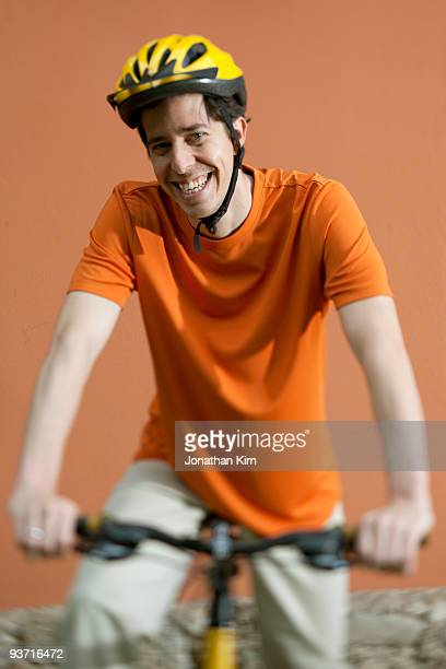 Thirty four year old man smiles on bike.