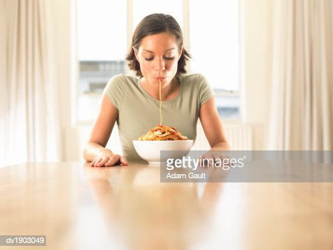Thirty something Woman Sitting at a Dining Table Eating Spaghetti : Stock Photo