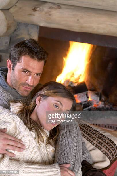Thirtysomething Couple Sitting by a Fire